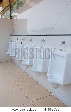 interior of white urinals in men bathroom toilet
