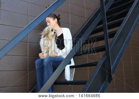 Girl holding her dog on the stairs.