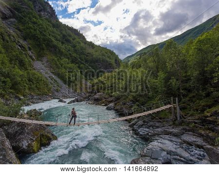 Aerial view of woman standing on the suspension bridge over a wild mountain river. Norway.