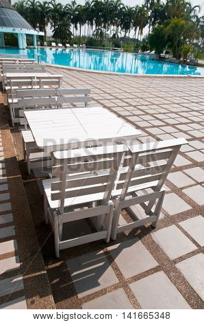 White wooden chair in swimming pool, outdoor