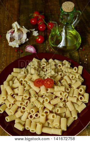closeup of a plate with cooked penne rigate on a table with garlic cloves, tomatoes and a glass cruet with olive oil on a rustic wooden table