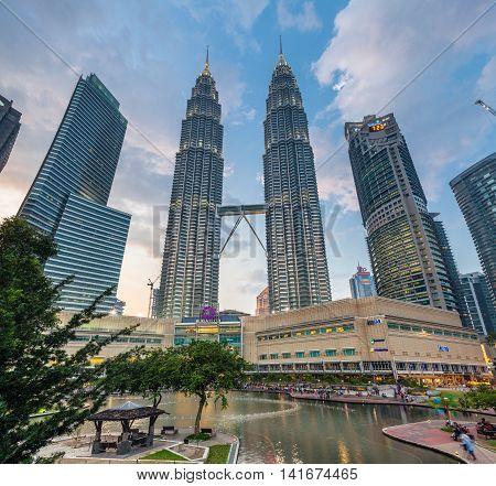 KUALA LUMPUR MALAYSIA - MARCH 14: Petronas TwinTowers and Suria KLCC shopping mall at sunset Kuala Lumpur Malaysia on March 14 2016.
