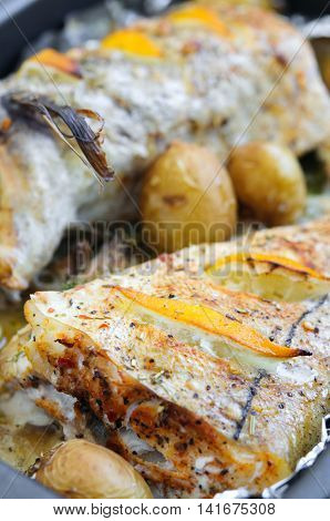 Baked haddock with lemon slices and small potatoes close-up