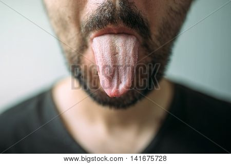 Adult unshaven man sticking tongue out selective focus
