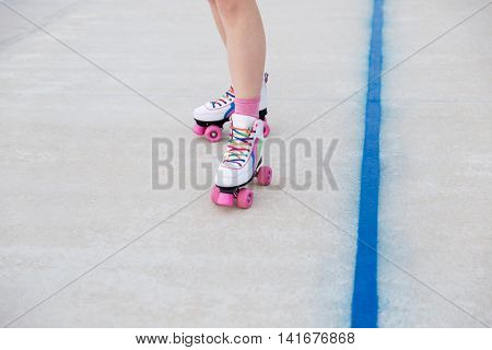 Close-up portrait of female legs in roller blades at the playground