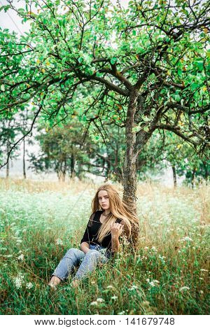 Girl in jeans outdoors. The girl near a tree.