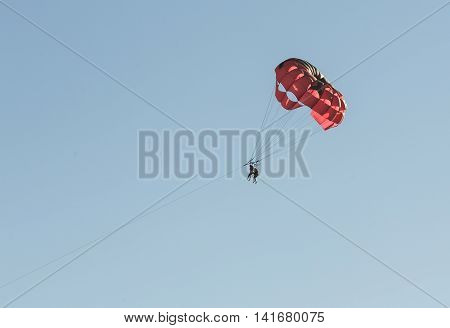 Parasailing on a red parachute over water Fort Myers. Florida