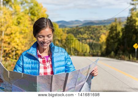 Asian hiker woman on adventure nature travel looking at map directions against autumn landscape during road trip. Happy tourist searching her way on car driving holidays in forest outdoors.