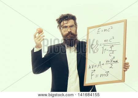 young handsome bearded man scientist or professor in glasses with long beard holding apple and teacher board with einstein formula and newtons law isolated on white background