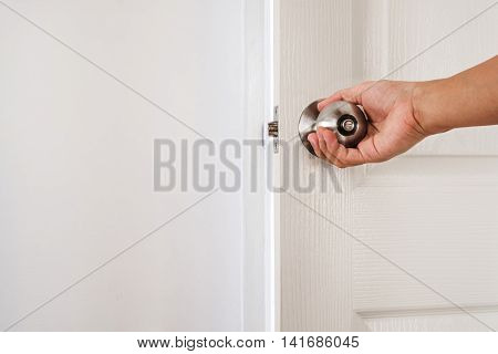 Hand holding door knob, white door and wall, with copy space
