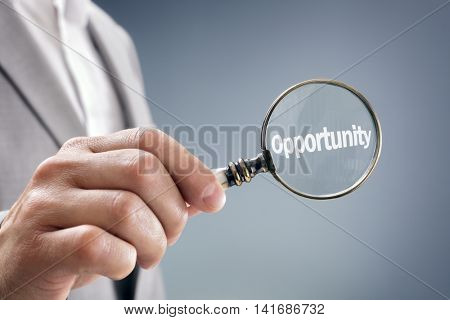 Businessman with magnifying glass searching for opportunity