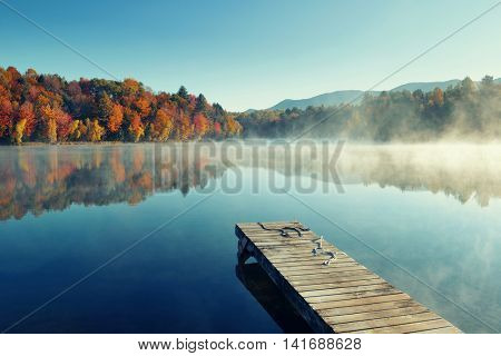 Autumn foliage and fog lake in morning with boat dock