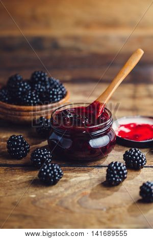 Fresh homemade blackberry jam in glass jar on a wooden background