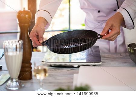 Man's hands hold frying pan. Pan of black color. New teflon kitchenware. Thin layer of oil.