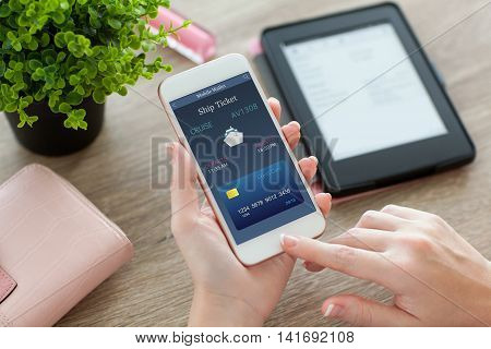 female hands holding white phone with online ship ticket in screen and e-rider on women table