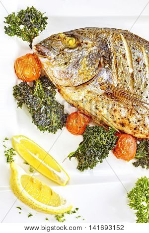Roasted Gilt Head Bream Fish On A White Plate.