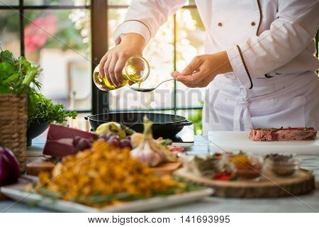 Jug pours liquid into spoon. Raw meat with spices. High quality olive oil. Plant fat required for recipe.