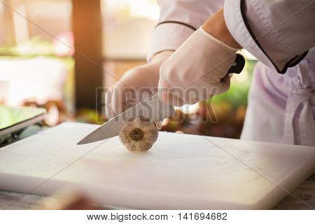 Hand with knife cuts garlic. Vegetable on white cooking board. Need a special ingredient. Chef knows his work well.