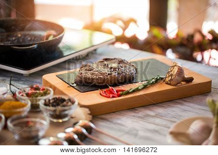 Cooked meat and rosemary. Chili peppers and roasted garlic. Ribeye steak from juicy beef. Most delicious food in restaurant.