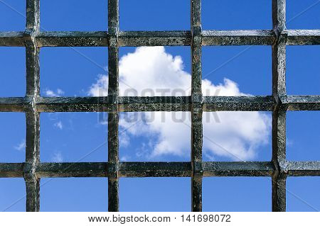 Metal jail bars with a blue sky with some clouds in the background as a concept of freedom wish