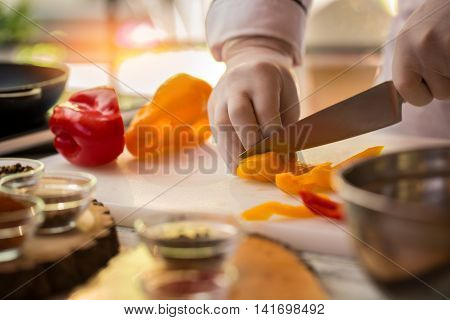 Hand with knife cuts paprika. Yellow pepper on cooking board. Chef prepares ingredient for ragout. Only freshest vegetables.