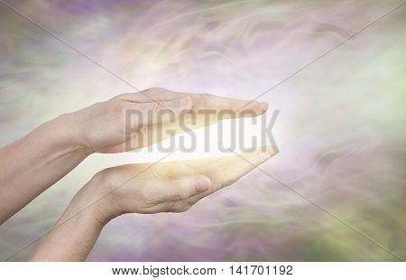 Golden healing aura - female hands held in parallel position with a golden glow between on a subtle  radiating light energy field streaming outwards with copy space