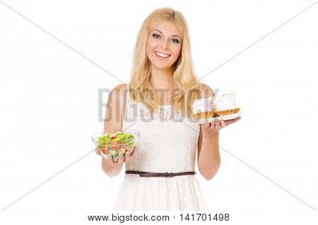 Half-length portrait of very beautiful woman holding small cake, fresh vegetables. Young housewife choosing sweets or healthy eating - cake and salad. Laughing at camera. Isolated on white background.