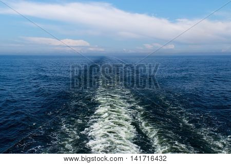 Track of ferryboat on blue sea water.