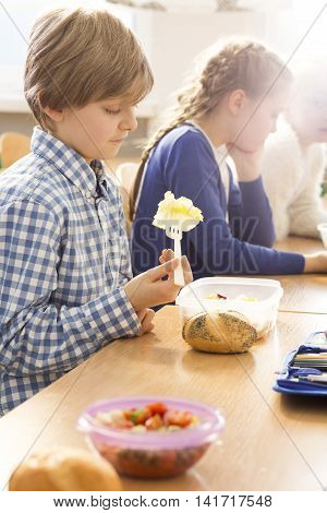Young boy sitting at a desk and looking at his packed lunch