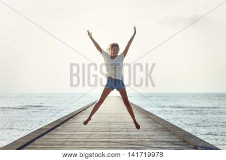 Happy Jumping Girl On The Pier