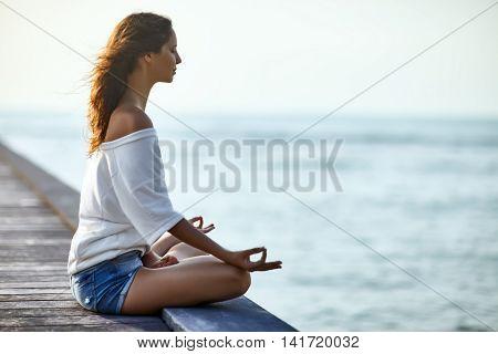 Woman Meditating In Lotus Pose On Pier