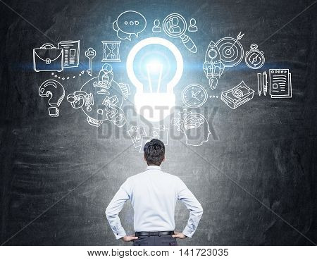 Man standing with back to camera looking at chalkboard with light bulb and different sketches on it. Concept of finding right way.