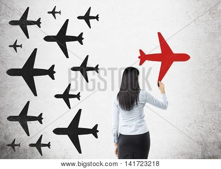 Woman in formal suit is drawing bright red airplane on concrete wall. There are drawings of black planes on the wall. Concept of original idea.