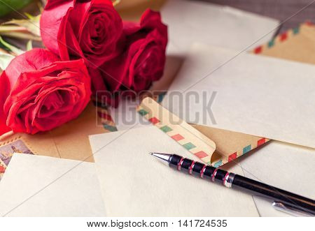 Vintage envelopes bouquet of red roses and sheets of paper scattered on the wooden table for writing romantic letters.
