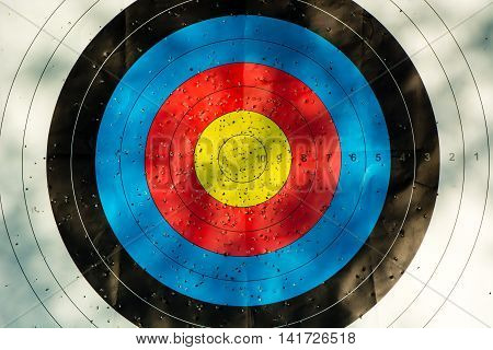 Archery target with arrow holes. Gold red blue and black competition target marked where arrows have penetrated