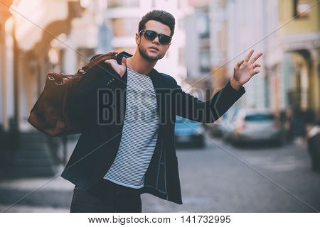 Taxi! Handsome young man in smart casual wear carrying bag on shoulder and gesturing while hitchhiking on the street