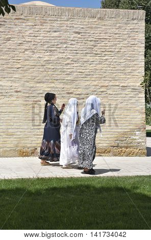 Bukhara Uzbekistan - August 05 2015: Uzbek pilgrims walking in the Central square of the memorial complex of BAHAUDDIN Naqshbandi in Bukhara.