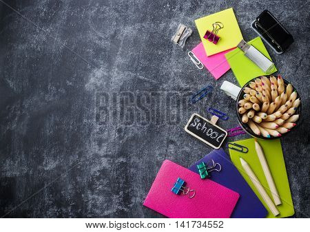 Education, back to school concept. School stationery, supplies, pencil, pen, note on a grunge chalkboard. Selective focus, copy space background, flat lay, top view