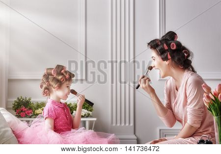 Happy loving family. Mother and daughter are doing hair and having fun. Mom and child doing your makeup sitting on the bed in the bedroom.
