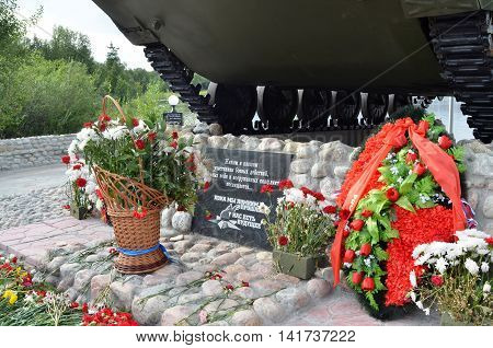 """MONCHEGORSK, RUSSIA - AUGUST 2016: Detail of monument - granite plaque with inscription: """"Living and fallen combatants, local wars and armed conflicts is dedicated. Long as we remember past - we have future"""""""