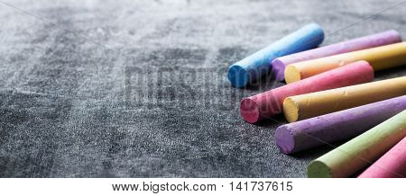 Education, back to school concept. Pieces of school chalk on old black chalkboard. Selective focus, copy space background