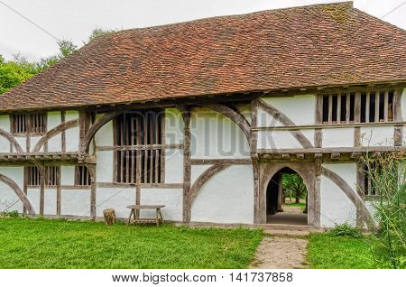 A reconstructed medieval building with red slate roof, wooden beams, lath, white plaster and arched entrance at the Singleton Museum in England.