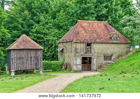 Reconstructed medieval buildings at Singleton Museum, Sussex, England, one of stone with tiled roof - stable , the other made of wooden planks raised off the ground with stone mushroom shaped stones, background of trees,