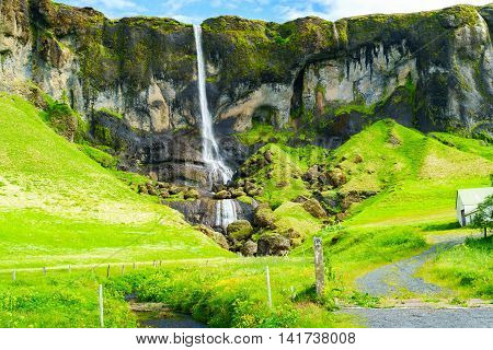 View of a high waterfall in southeast Iceland in summer
