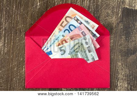 Red envelope with Euro bills over wooden background
