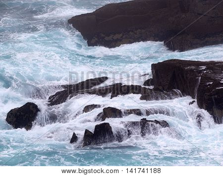 Wild waves crashing against a rock on Dingle peninsula Ireland