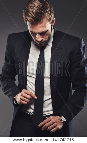 Handsome young man in a black suit adjusting his neck tie standing against a gray background