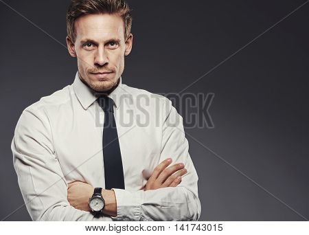 Handsome young businessman in a shirt and tie looking focused standing with arms crossed against a gray background