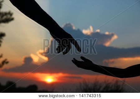 silhouette of the parent holds the hand of a small child