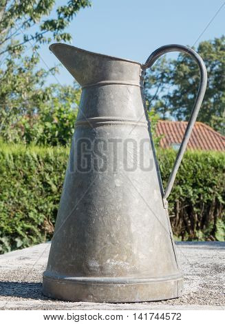 an old pewter pitcher in the garden